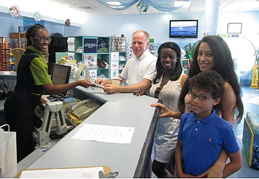 "Pictured above from left, presenting their  ""free spending money vouchers"" to Leeanne  Brathwaite of Atlantis Submarines is a family from the United Kingdom  Mr. Martin Hoare, Mrs. Nana Anima-Marfoh, Georgia and Eben Marfoh-Hoare."