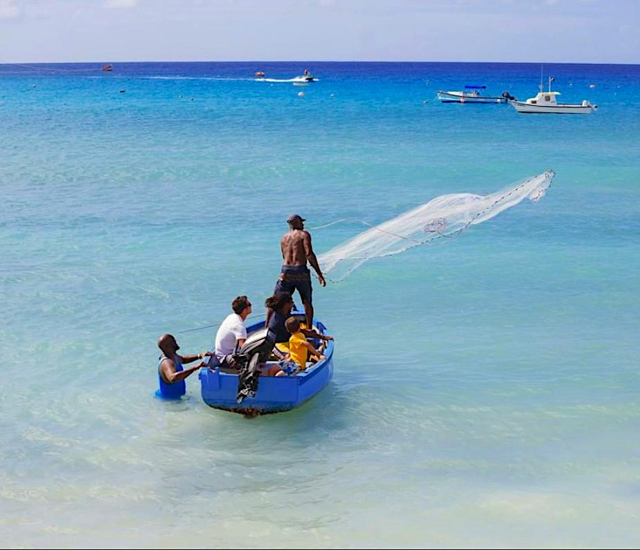 Casting the net off the coast along a Barbados beach