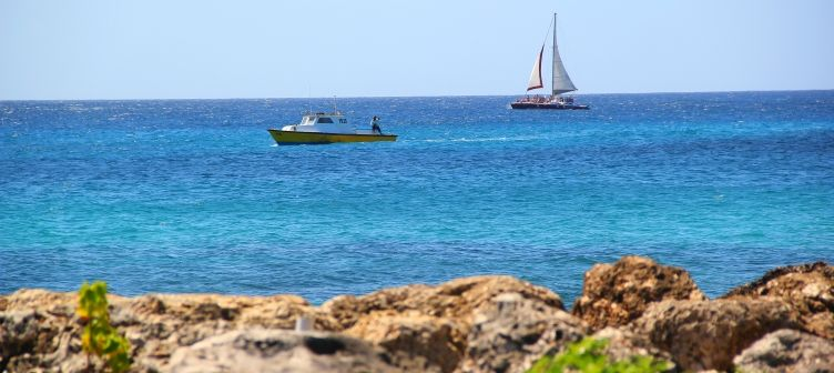 Fishing boat and catamaran sailing past Trevor's Way